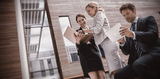 Businesspeople using laptop and tablet. In office premises Royalty Free Stock Photo