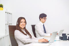 Businesspeople using laptops. Businesswoman with headset and businessman using laptops in bright office. Sideview Stock Photo