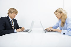 Businesspeople using laptops at desk in office Royalty Free Stock Images