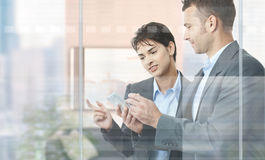 Businesspeople using mobile stock image