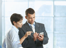 Businesspeople using mobile. Two businesspeople standing in office lobby , looking at smart mobile phone, smiling royalty free stock photo