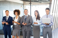 Businesspeople using mobile phone, lap top and digital tablet. Businesspeople standing in a row and using mobile phone, lap top and digital tablet in offic Stock Images