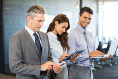 Businesspeople using mobile phone, lap top and digital tablet. Businesspeople standing in a row and using mobile phone, lap top and digital tablet in office Royalty Free Stock Images