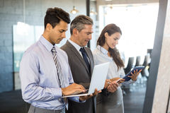 Businesspeople using mobile phone, lap top and digital tablet. Businesspeople standing in a row and using mobile phone, lap top and digital tablet in office Royalty Free Stock Photo