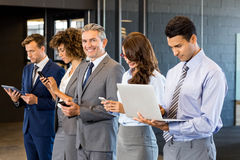 Businesspeople using mobile phone, lap top and digital tablet. Businesspeople standing in a row and using mobile phone, lap top and digital tablet in office Stock Images