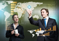 Businesspeople using modern technologies. Young businessman and businesswoman working in cooperation with virtual panel Royalty Free Stock Photography