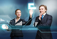 Businesspeople using modern technologies. Young businessman and businesswoman working in cooperation with virtual panel Royalty Free Stock Images
