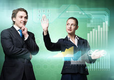 Businesspeople using modern technologies. Young businessman and businesswoman working in cooperation with virtual panel Stock Photography
