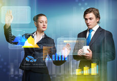 Businesspeople using modern technologies. Young businessman and businesswoman working in cooperation with virtual panel Stock Photos