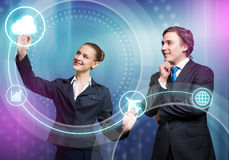 Businesspeople using modern technologies. Young businessman and businesswoman working in cooperation with virtual panel Stock Image