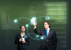 Businesspeople using modern technologies. Young businessman and businesswoman working in cooperation with virtual panel Royalty Free Stock Image