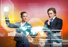 Businesspeople using modern technologies. Young businessman and businesswoman working in cooperation with virtual panel Royalty Free Stock Photo
