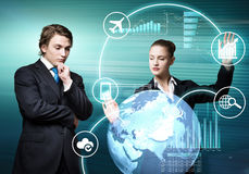 Businesspeople using modern technologies. Young businessman and businesswoman working in cooperation with virtual panel Stock Images