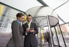 Businesspeople Using PDA In Front Of Revolving Door Stock Images