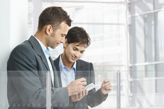 Businesspeople using smartphone. Two businesspeople standing in modern office building with glass walls, using smart mobile phone royalty free stock images