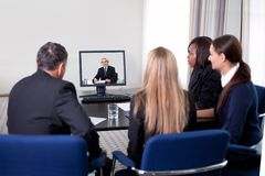 Businesspeople at a video conference. Group of successful young businesspeople at a video conference in the office royalty free stock photography