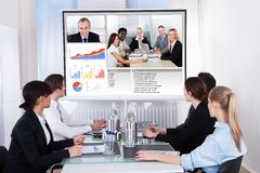 Businesspeople in video conference at business meeting. Businesspeople Sitting In A Conference Room Looking At Screen Royalty Free Stock Photos