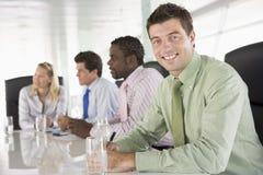 Businesspeople vier in bestuurskamer het glimlachen Stock Fotografie