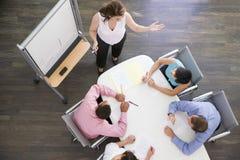 Businesspeople vier bij bestuurskamerlijst Stock Foto's