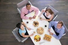 Businesspeople vier die bij bestuurskamerlijst eet Stock Foto's