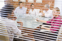 Businesspeople vijf in bestuurskamer door venster Stock Foto