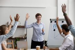 Diverse company members headed by business trainer raising hands stock photos