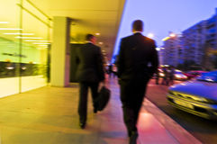 Businesspeople walking. Business people walking on the pavement of a commercial building in the evening Royalty Free Stock Images