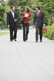 Businesspeople Walking Through City Park Royalty Free Stock Images