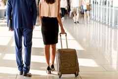 Businesspeople walking with luggage at airport Stock Images