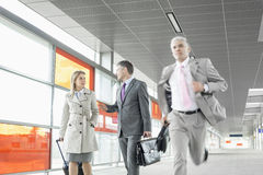 Businesspeople walking while male colleague running in railroad station Royalty Free Stock Photo