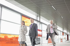 Businesspeople walking while male colleague running in railroad station Stock Photos