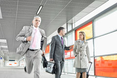 Businesspeople walking while male colleague running in railroad station Royalty Free Stock Image