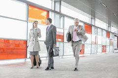 Businesspeople walking while male colleague rushing in railroad station royalty free stock photos