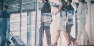 Businesspeople walking in office. Businesspeople holding suitcase walking in office royalty free stock photos