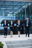 Businesspeople walking in office premises. Confident businesspeople walking in office premises Royalty Free Stock Photos