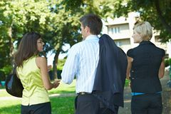 Businesspeople walking in park. Young businesspeople walking through park, talking stock photography