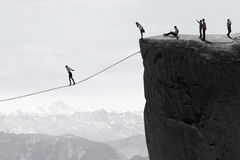 Businesspeople walking on the rope over the cliff Stock Photo