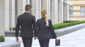 Businesspeople walking on the street of an business center, slow motion. Two business colleagues in discussion, businesspeople walking on the street of an stock video