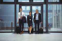 Businesspeople walking together with luggage. In office Royalty Free Stock Photos