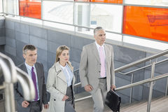 Businesspeople walking up stairs in train station Stock Image