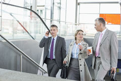 Businesspeople walking up stairs in train station Stock Photography