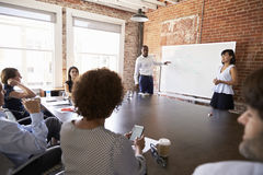 Businesspeople At Whiteboard Give Presentation In Boardroom Royalty Free Stock Images