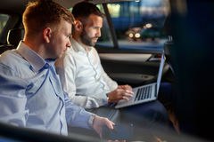 Businesspeople work on late night in back seat of car Stock Image