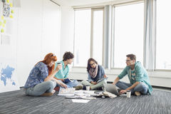 Businesspeople working on floor at creative work space Stock Photography