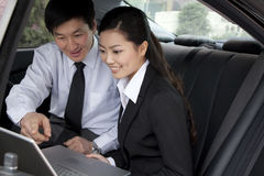 Businesspeople working on laptop in back of car Royalty Free Stock Photography