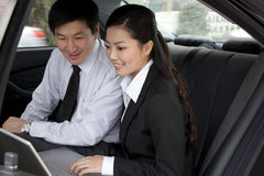 Businesspeople working on laptop in back of car Royalty Free Stock Image