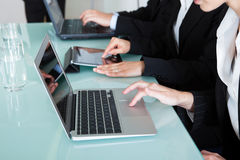 Businesspeople working on laptops and tablets Stock Photos