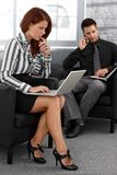 Businesspeople working in office lobby Royalty Free Stock Image