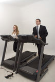 Businesspeople Working Out. Male and female business colleagues on a treadmill together. Isolated against a studio background Royalty Free Stock Photos