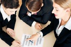 Businesspeople working on spreadsheet Stock Photo